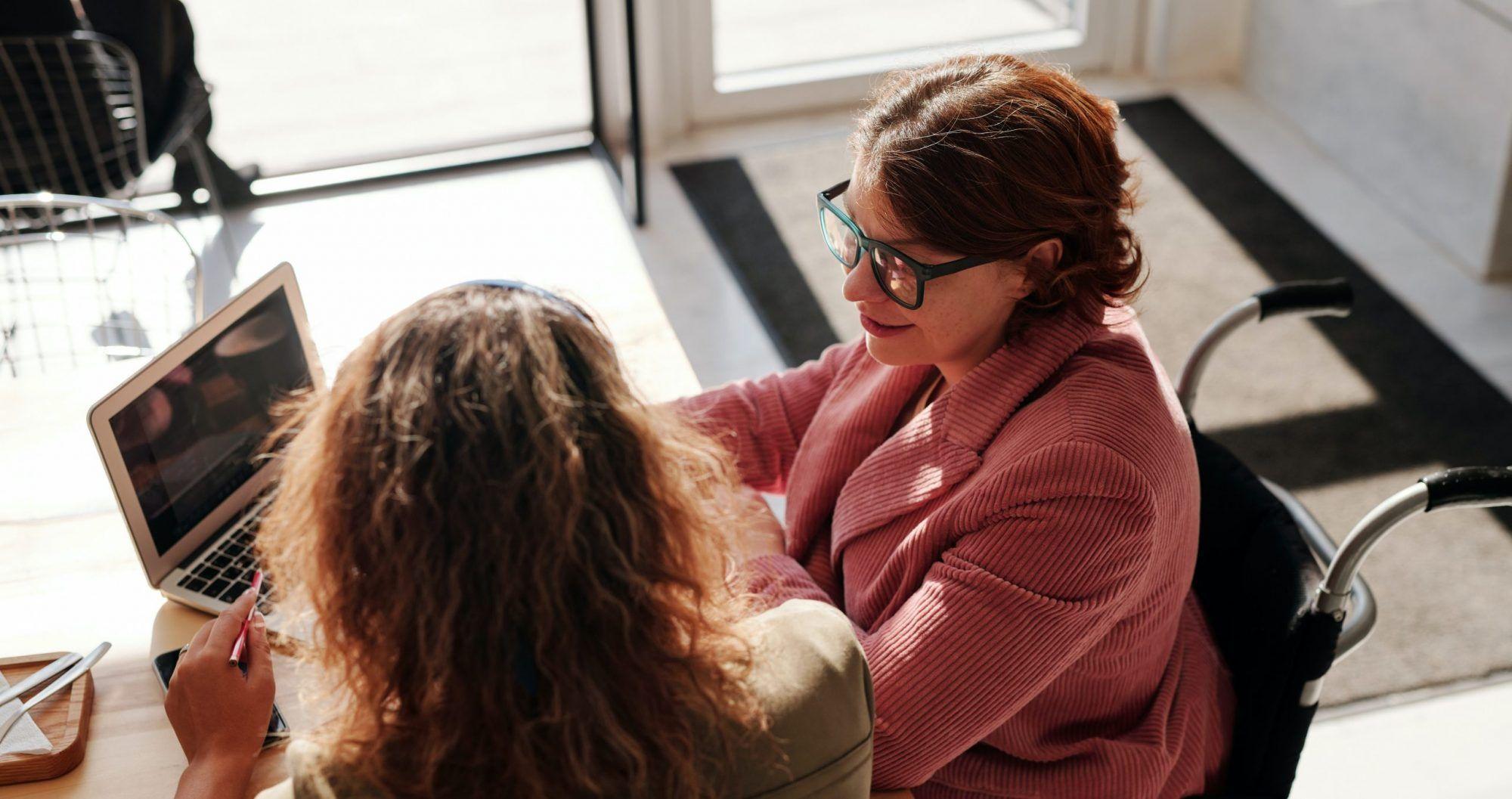 Dos mujeres hablando por una computadora, a la derecha una mujer es usuaria de silla de ruedas, a la izquierda una mujer mirando hacia atrás.